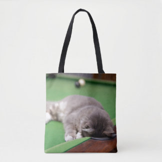 Kitten playing on pool table. tote bag