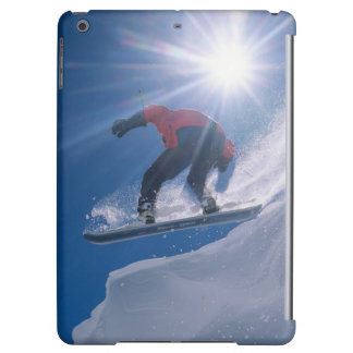 Man jumping off a large cornince on a snowboard