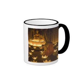 Monks lighting khom loy candles and lanterns for ringer mug