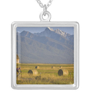 Road bicyclists race down back country road in square pendant necklace
