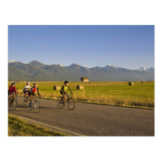 Road bicyclists ride down a back country road postcard
