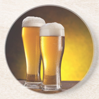 Two glasses of beers on a wooden table coasters