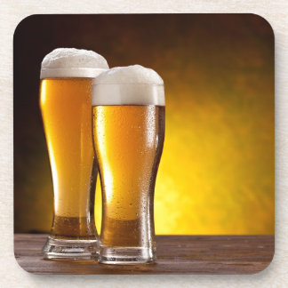 Two glasses of beers on a wooden table drink coasters