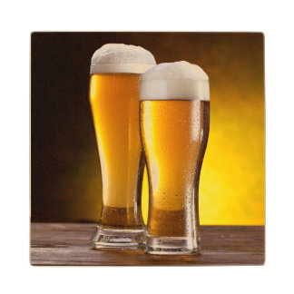 Two glasses of beers on a wooden table maple wood coaster