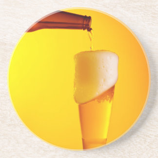 Waiter pouring beer, glass of a cold drink drink coasters