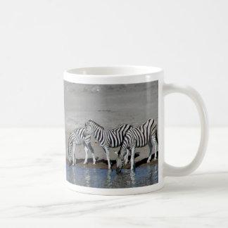Zebras and giraffe at the local watering hole Mug